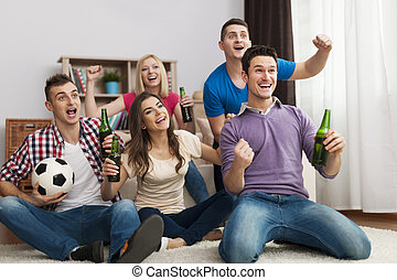 Group of friends enjoying soccer in TV