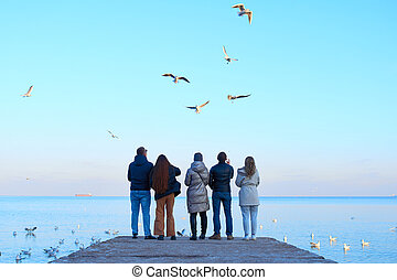 Group of friends feeding seagulls on the beach