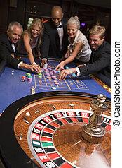 Group of friends gambling in casino
