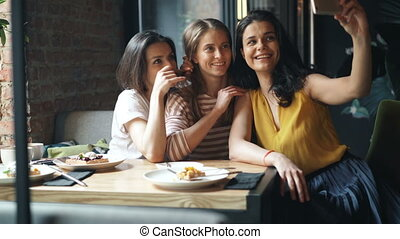 Group of friends girls taking selfie in cafe holding...