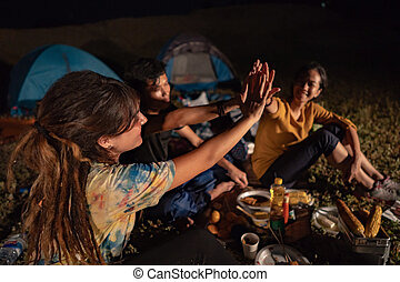 group of friends giving high five while sitting around campfire