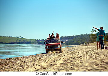Group of friends go on the shore of Lake Baikal in a car.