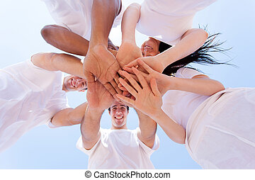 group of friends hands together - underneath view of group...