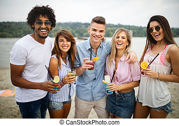 Group of friends hanging out with cocktails at the beach