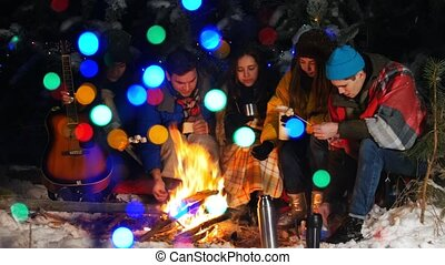 Group of friends having a good time by the fire in the...