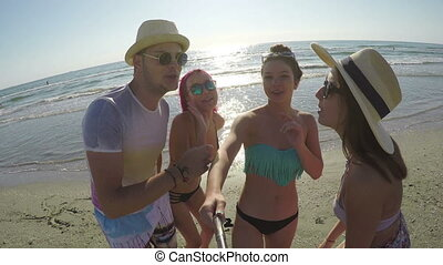 Group of friends having a selfie and partying on the beach