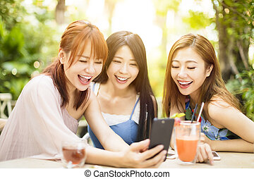 Group of friends having fun and looking at smart phone