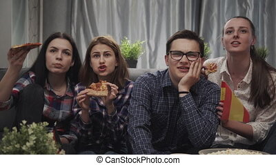 Group of friends having fun at home, watching game and enjoying together. People are watching football match at home, eat pizza. Spain and Germany.