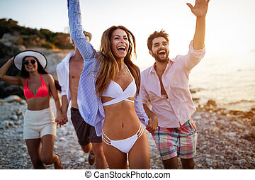 Group of friends having fun on the beach on vacation