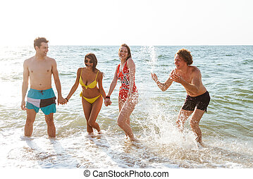 Group of friends having fun on the beach outdoors.