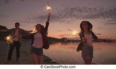Group of friends having fun running on the beach with sparklers.
