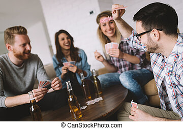 Group of friends having fun while playing cards