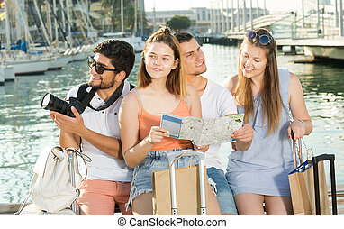 Group of friends having map and looking for route in town