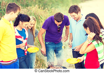 group of friends having picnic on the beach