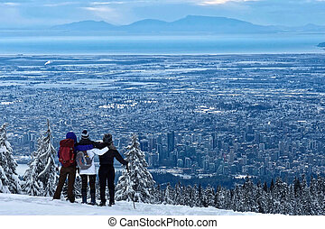 Group of friends hiking Cypress Mountain looking at Vancouver Downtown view in winter.