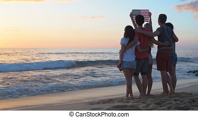 Group of friends holding american flag on the beach 4k