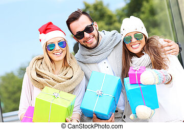 Group of friends holding Christmas presents