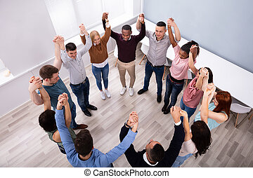 Group Of Friends Holding Each Other's Hands Cheering