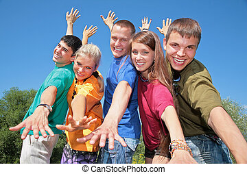 Group of friends in multicolor  shirts make gestures by hands