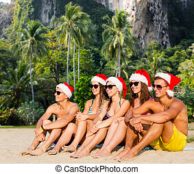 group of friends in santa helper hats on beach - travel,...