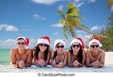 group of friends in santa helper hats on beach - friendship,...