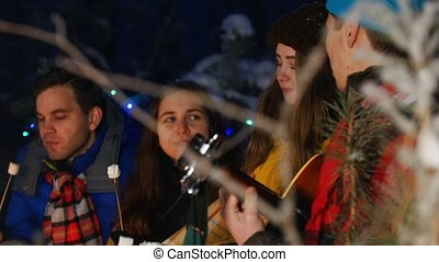 Group of friends in winter forest having a good time. Sitting near the bonfire. Young man playing guitar and everyone listening his playing
