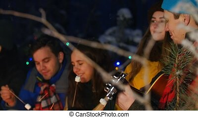 Group of friends in winter forest having a good time. Sitting near the bonfire. Young man playing guitar