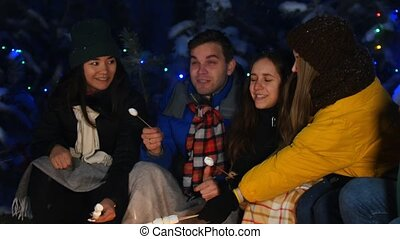 Group of friends in winter forest having a good time. Sitting near the bonfire. Young man playing guitar and everyone enjoying it