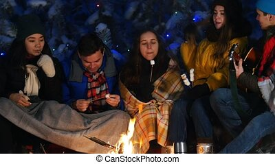 Group of friends in winter forest. Sitting near the bonfire and eating marshmallow. Spending time together and playing guitar