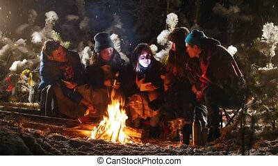Group of friends in winter forest. Sitting near the bonfire...