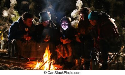 Group of friends in winter forest. Sitting near the bonfire,...