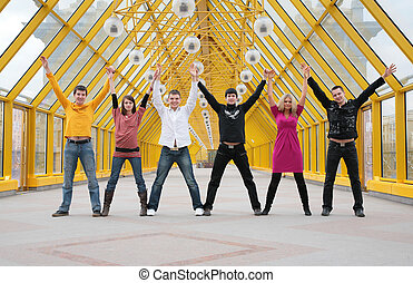 group of friends it stand taking hands and rising them on footbridge