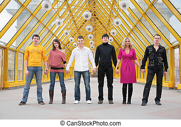 group of friends it stand taking hands on footbridge