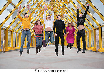 group of friends jump on footbridge