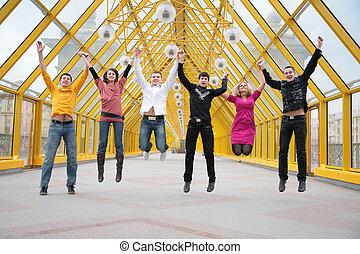 group of friends jump on footbridge taking as hands
