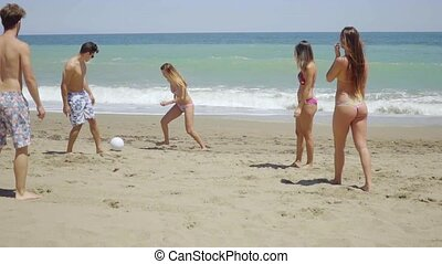 Group of Friends Kicking Ball on Sunny Beach