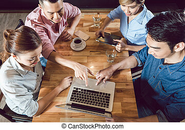Group of friends looking at laptop in the restaurant