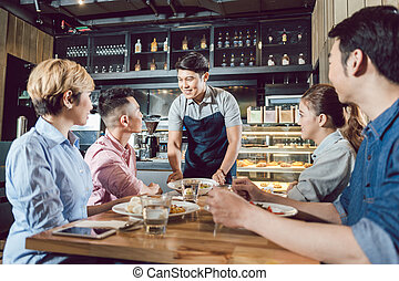 Group of friends looking at waiter serving food