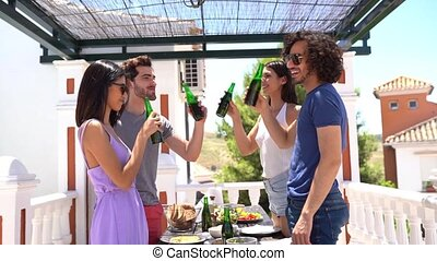 Group of friends making a toast with beer bottles in the ...