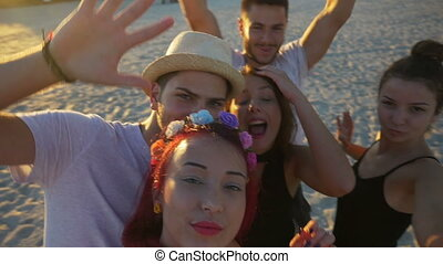 Group of friends making silly faces and fooling around on a...
