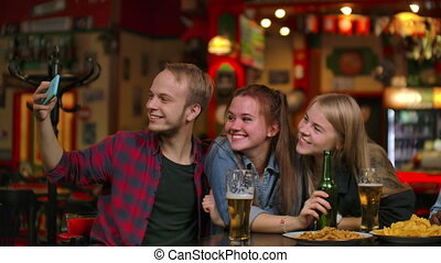 group of friends man and two girls take selfie in a bar...