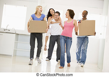 Group of friends moving into new home smiling