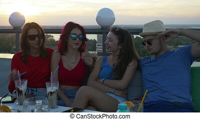 Group of friends on a rooftop bar having a chat and enjoying a drink