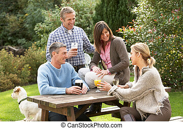 Group Of Friends Outdoors Enjoying Drink In Pub Garden