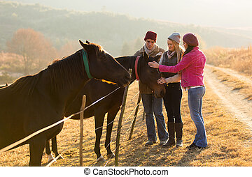 group of friends petting horses