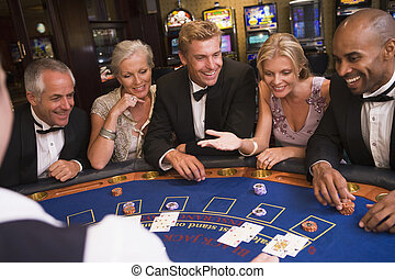 Five people sitting around blackjack table in casino