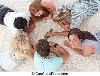 Group of friends playing spin the bottle - Group of friends...