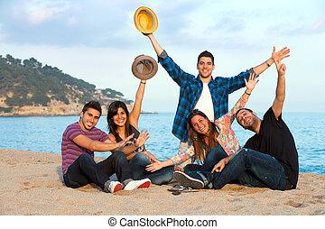 Group of friends raising hands on beach.