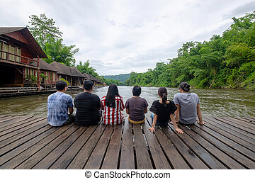Group of Friends Relaxing on the Wooden Float Above the River