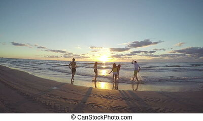 Group of friends running on a sandy wet beach towards the sea and teasing each other in the water